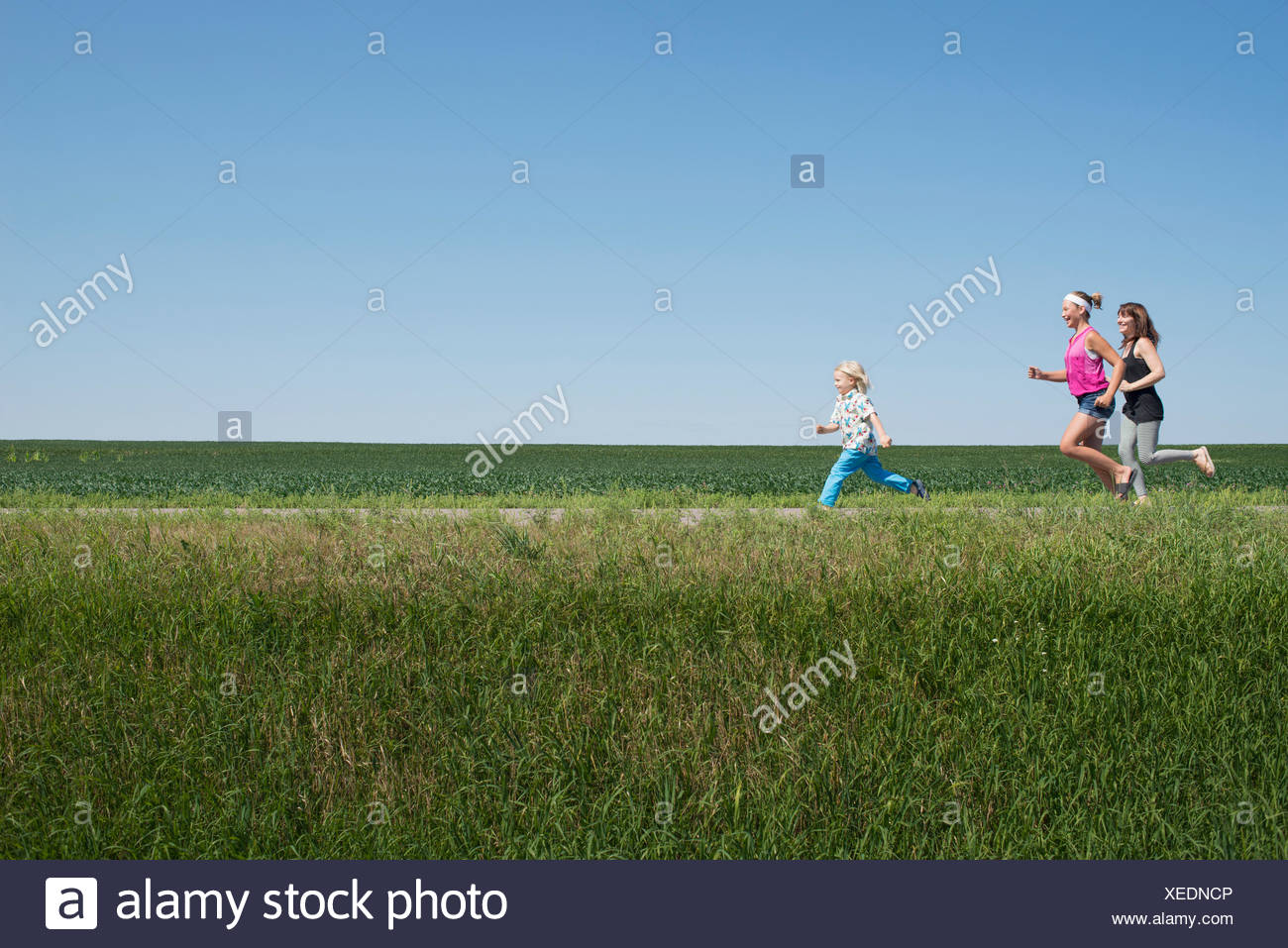 Three people running through field - Stock Image