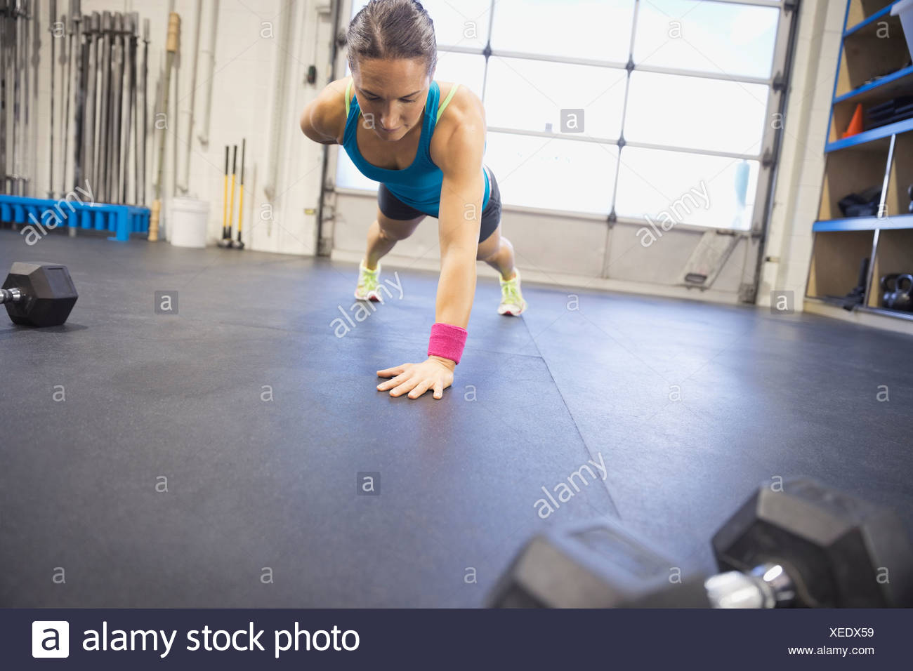 Determined woman doing one arm push-ups in gym - Stock Image