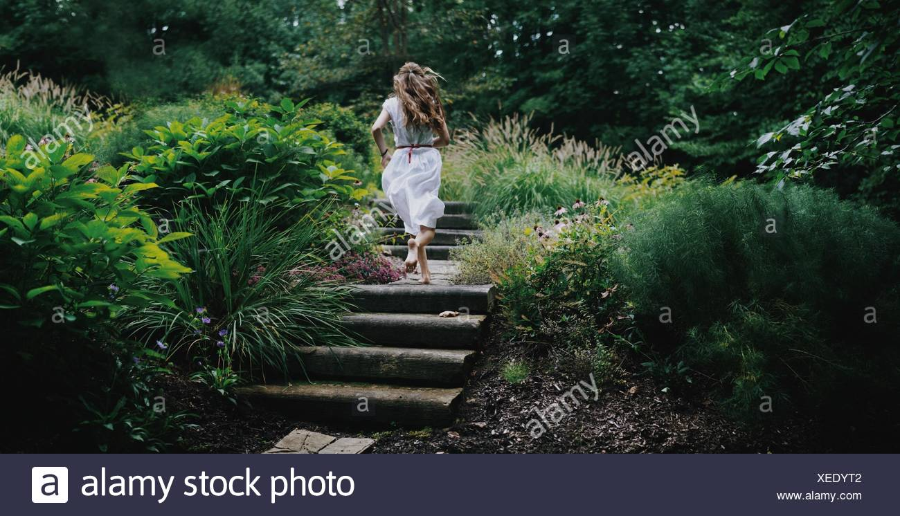 Rear view of young woman running up steps in a garden - Stock Image
