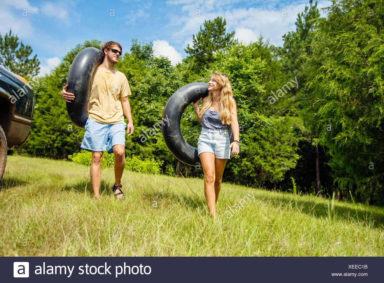 A young couple getting ready to tube down a river. - Stock Image