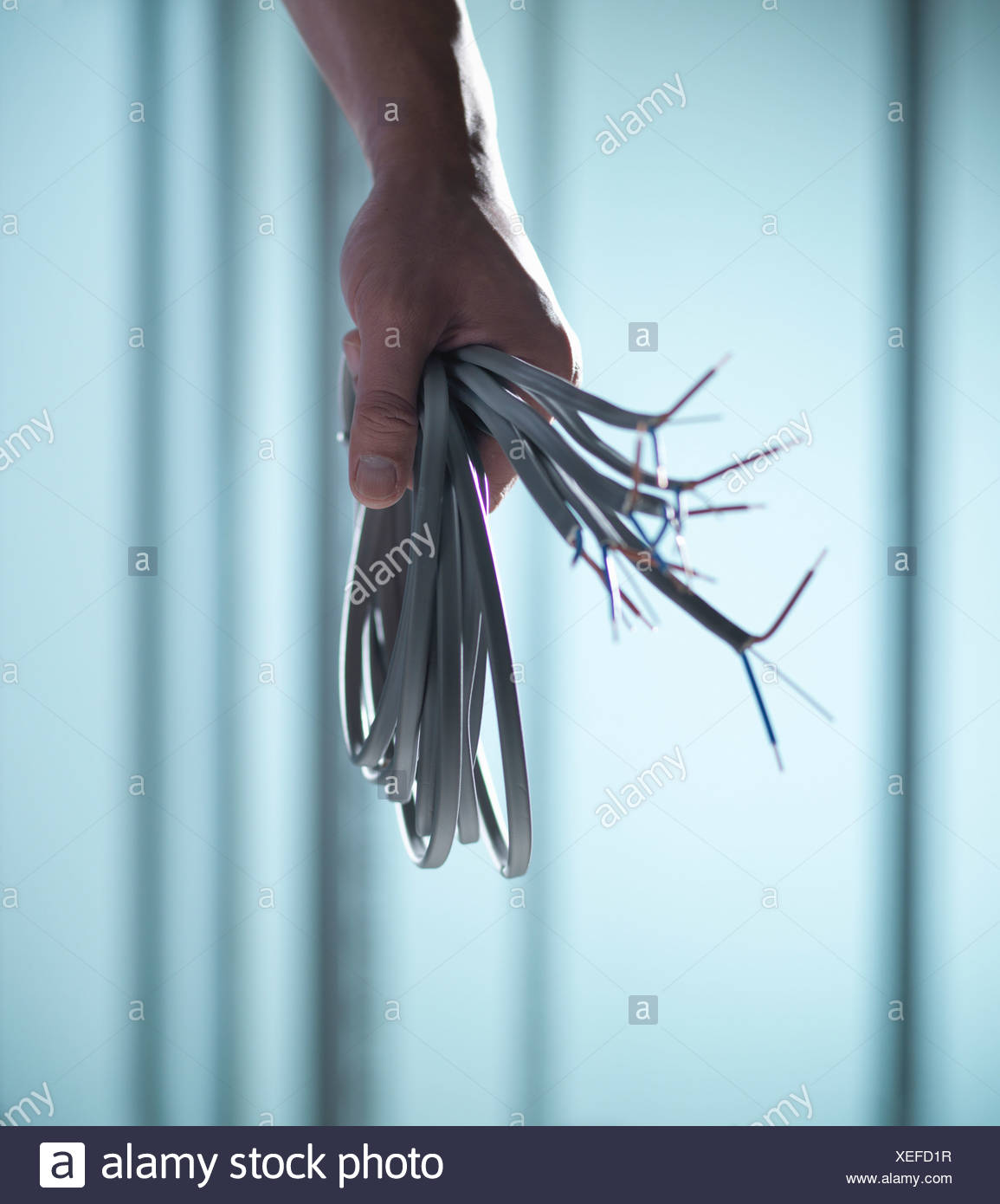Close up of hand holding cords - Stock Image