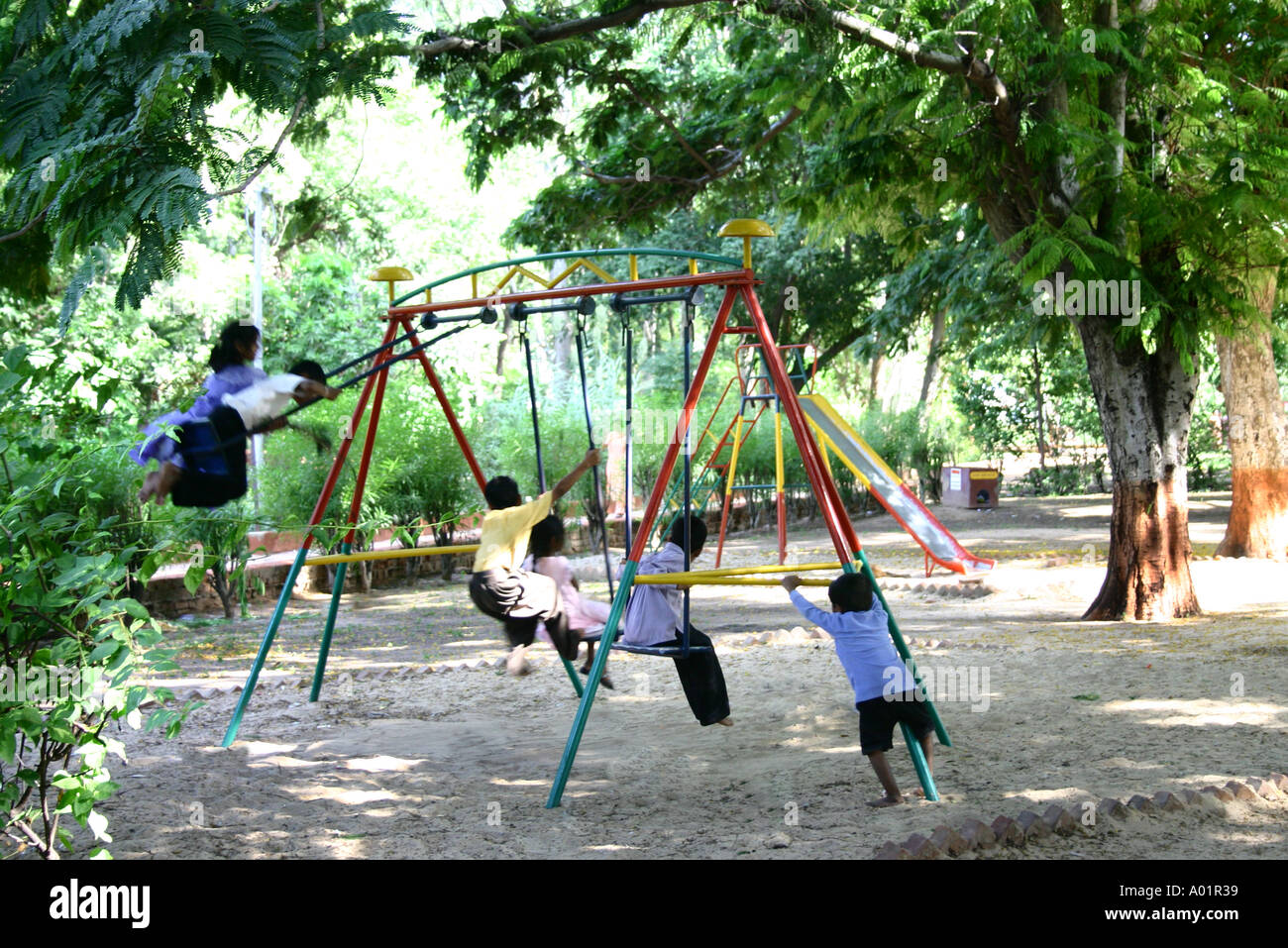 Children boys and girls playing and enjoying on swings in ...
