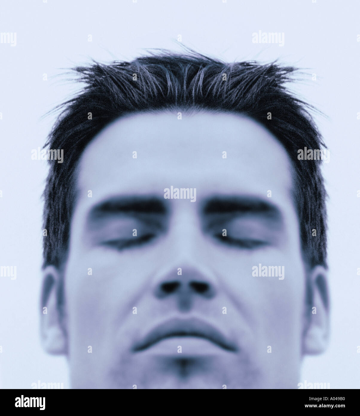 Close up portrait of young man  eyes closed  blue toned Stock Foto