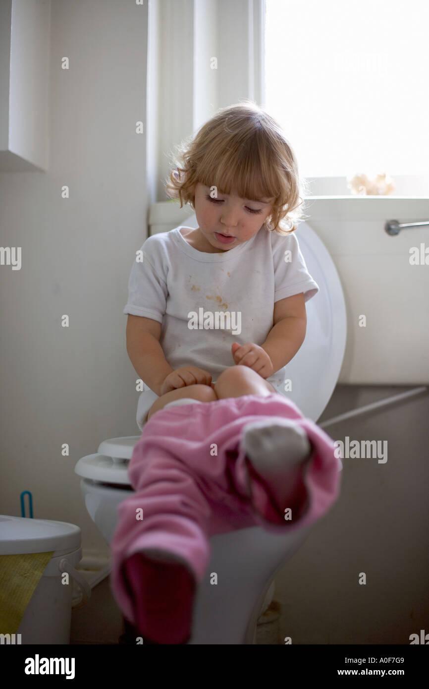 Young girl sitting on toilet Stock Photo: 5701704 - Alamy