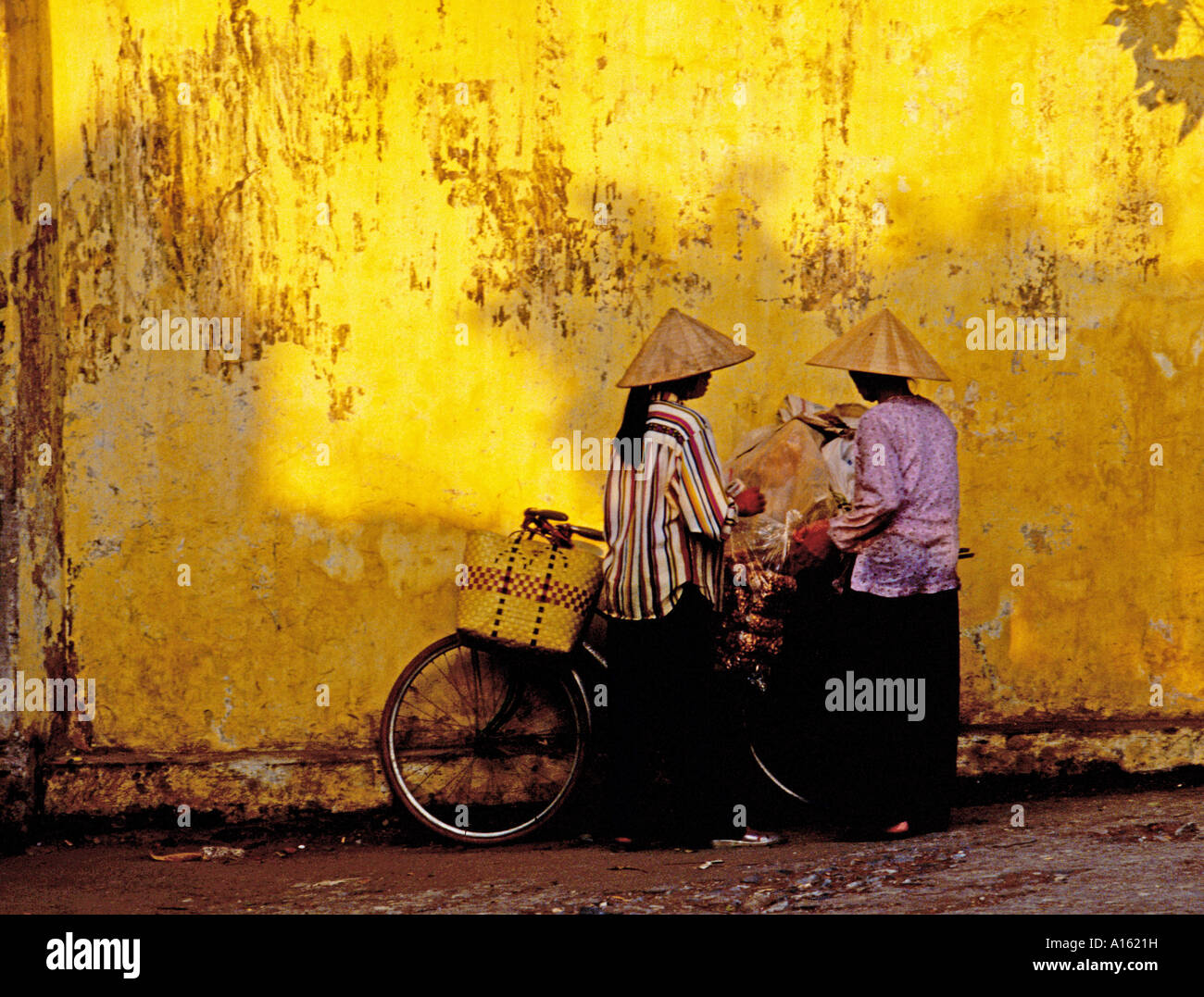 Two women with conical hats and bicycles Hanoi Vietnam. Stock Foto