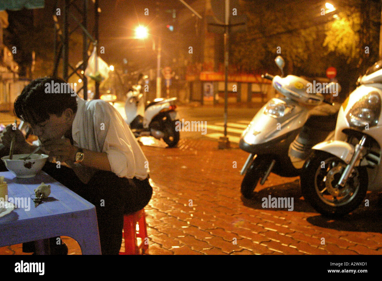 Stock Photo - A man eating at a late night food stall with scooters  on the pavement, Saigon, Vietnam