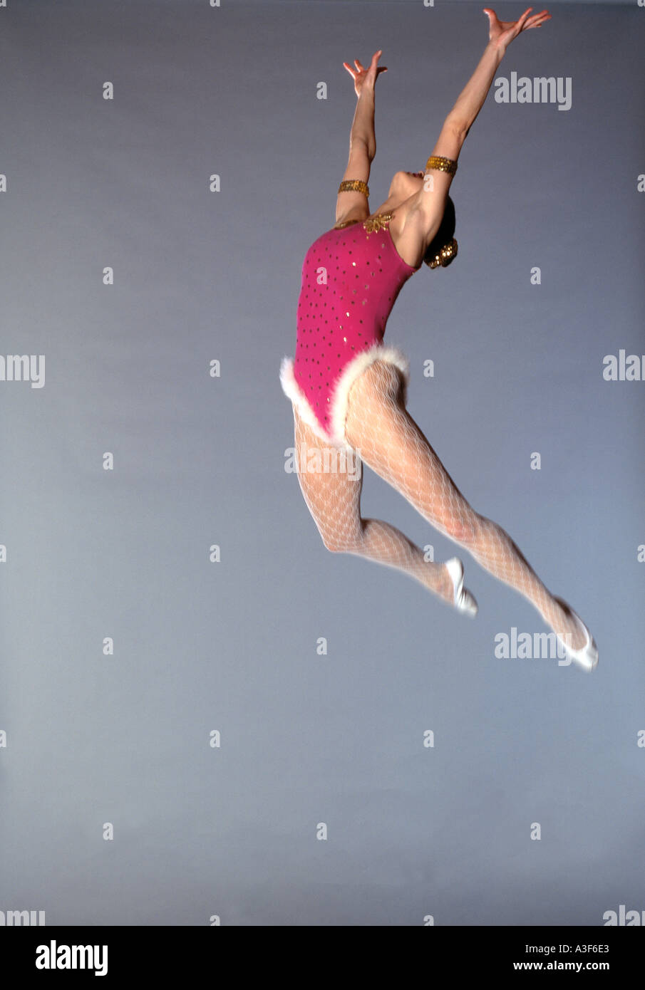 trapeze artist flying through the air grey background Stock Foto