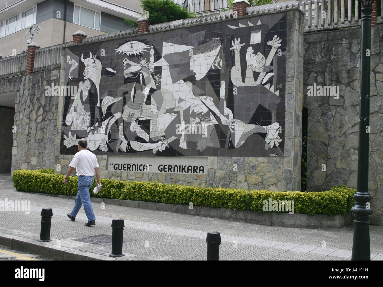Man walking past mural of picasso 39 s guernica in the basque for Mural guernica