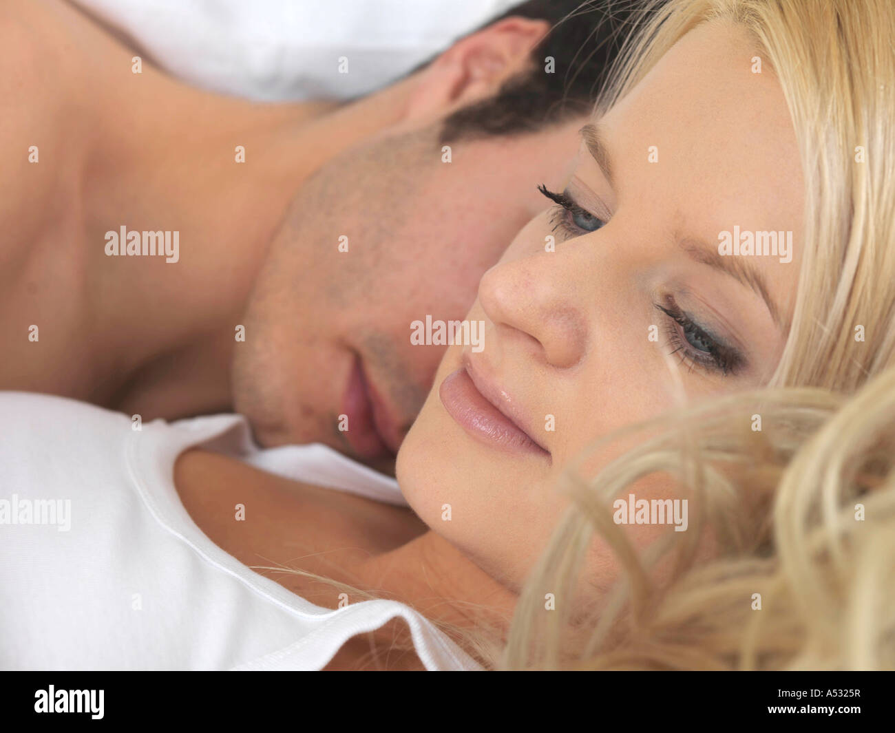 Young Couple in Bed Thoughtful and Worried Over A Relationship Breakdown or a Partner Cheating or Divorce Looking Stock Photo