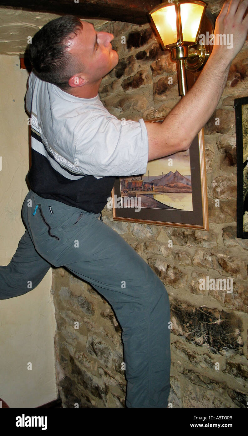 Young man indoor climbing the walls in an Inn after a few beers during a stag party weekend Stock Photo
