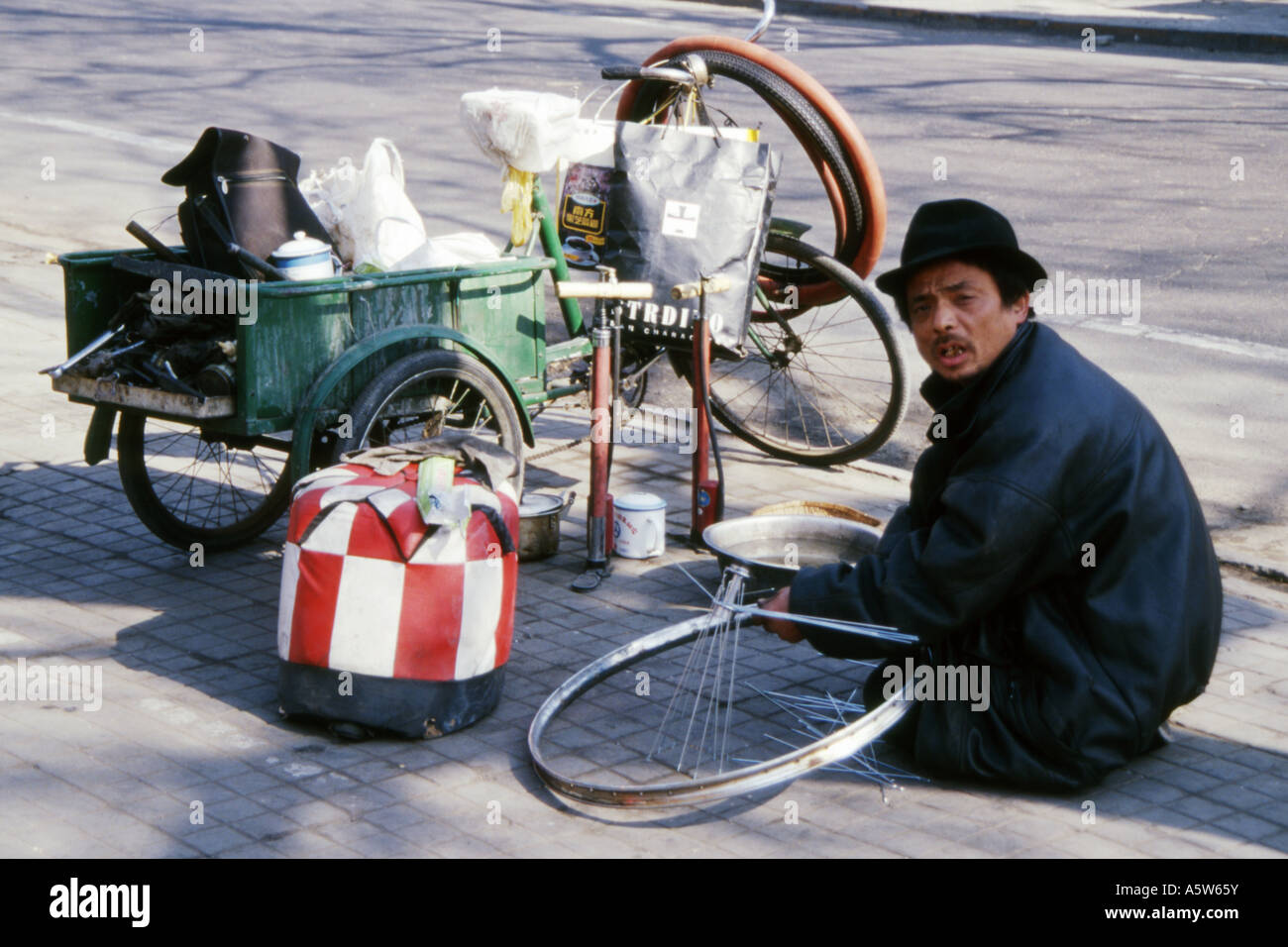 Local bicycle repair man working on a bicycle wheel at the roadside,Beijing,China. Stock Photo
