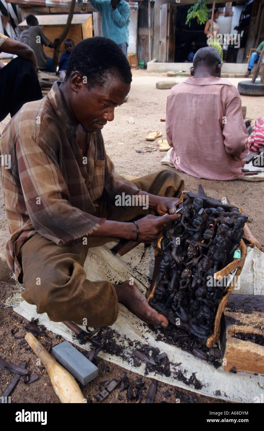 Makonde carver with ebony carving at mwenge market dar es