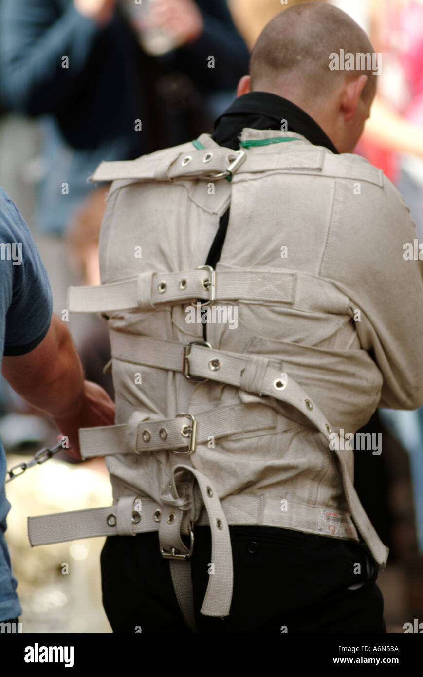 straight jacket street entertainer mad looney mental health handcuff tied up chain lock locked key strap escapologist Stock Photo