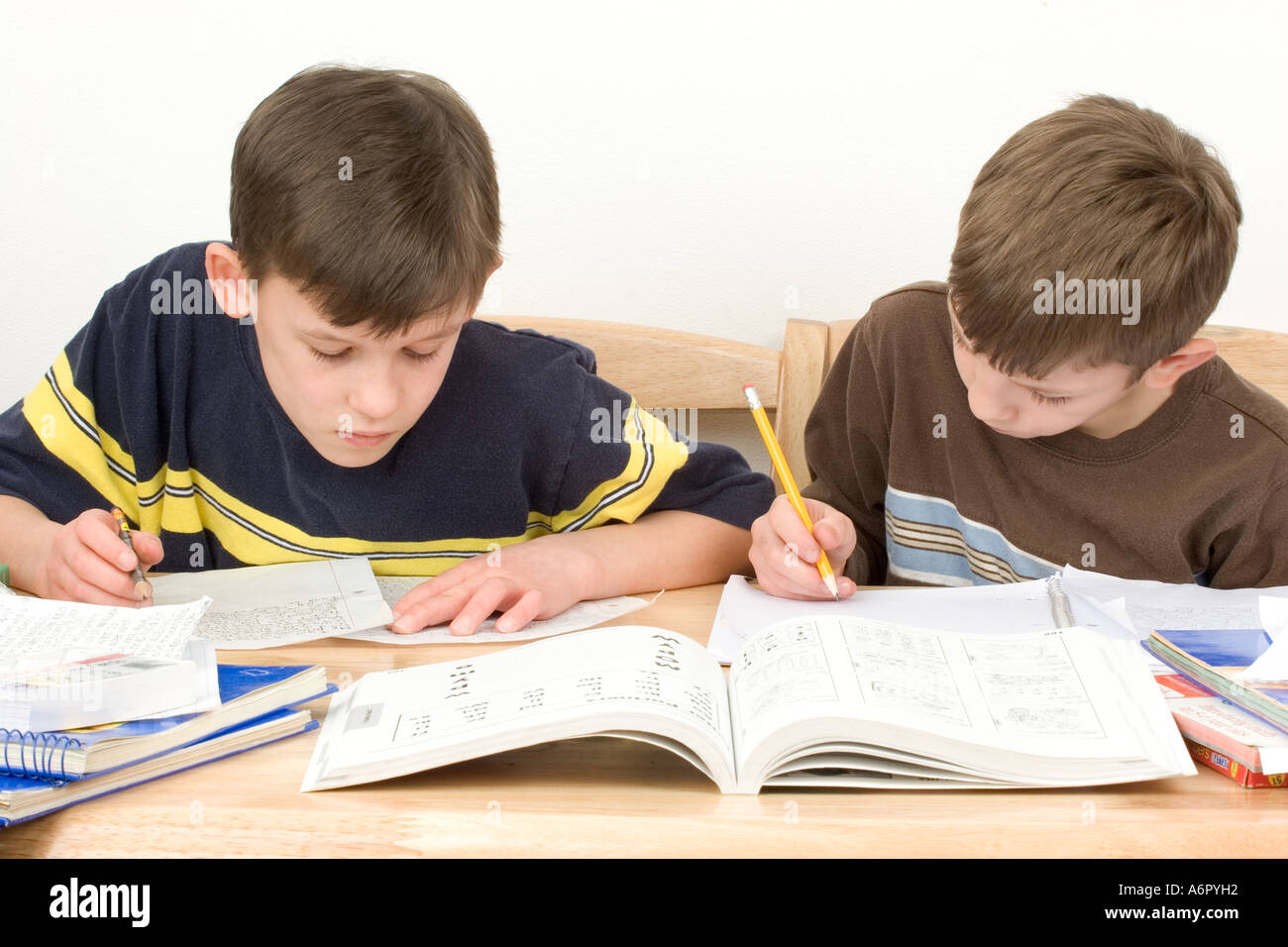 Boys doing home work study writing in book and reading