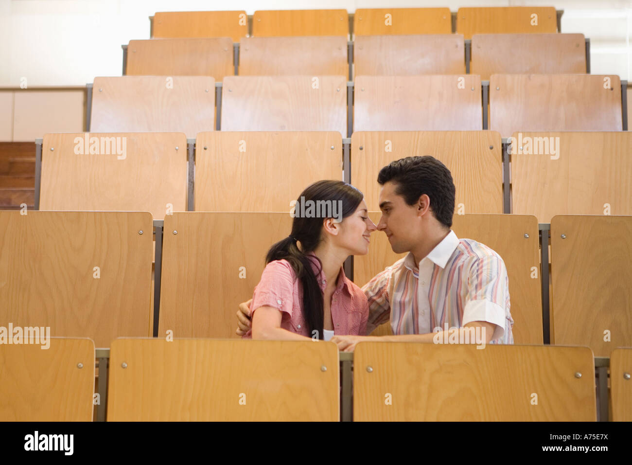 Students kissing in empty classroom Stock Foto