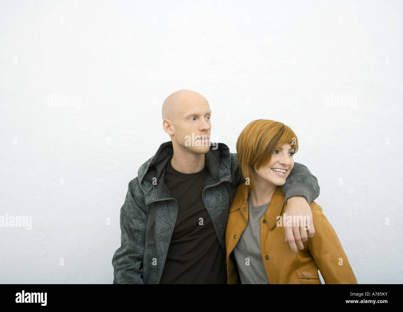 Young couple, man with arm around woman's shoulder, both ...