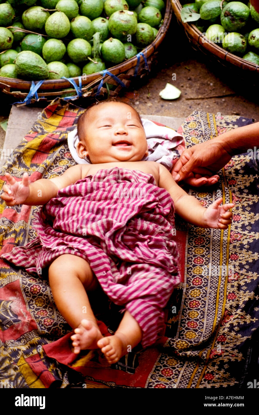 Smiling baby wrapped ina traditional Khmer scarf krama at a street market in Phnom Penh Stock Photo