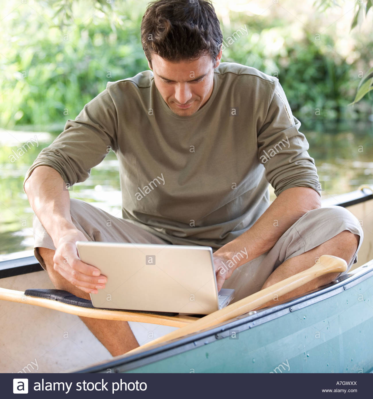 Young man sitting in a boat working on a laptop Stock Foto