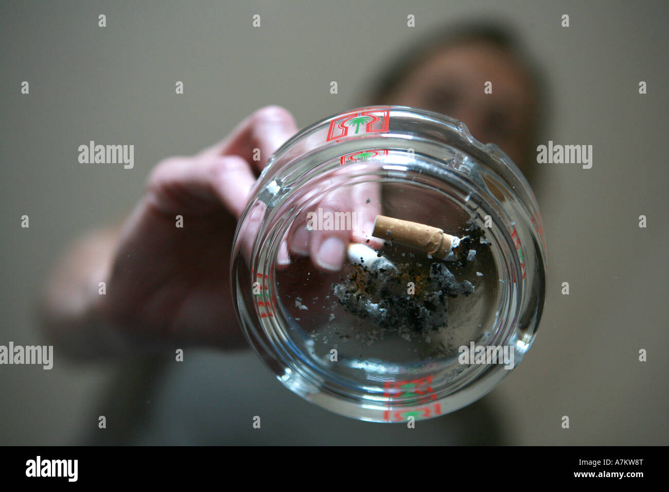 Smoker extinguishes a cigarette into a used ashtray on top of a glass coffee table in pub restaurant public building Stock Photo