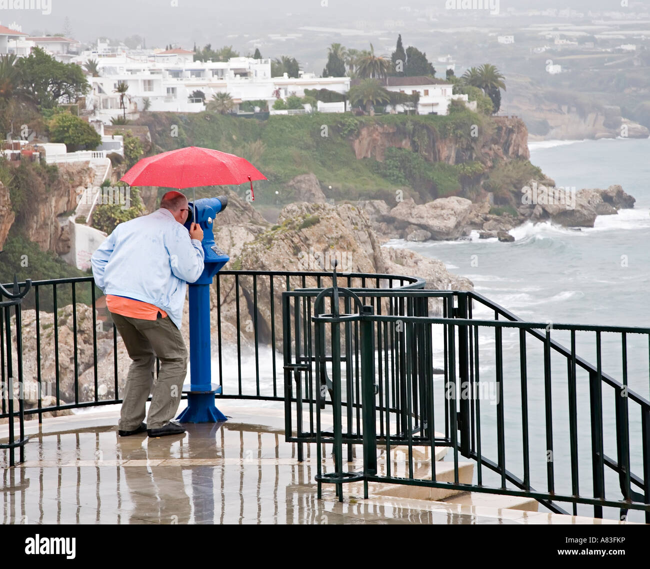 tourist with umbrella in pouring rain using seaside telescope balcon stock photo royalty free. Black Bedroom Furniture Sets. Home Design Ideas