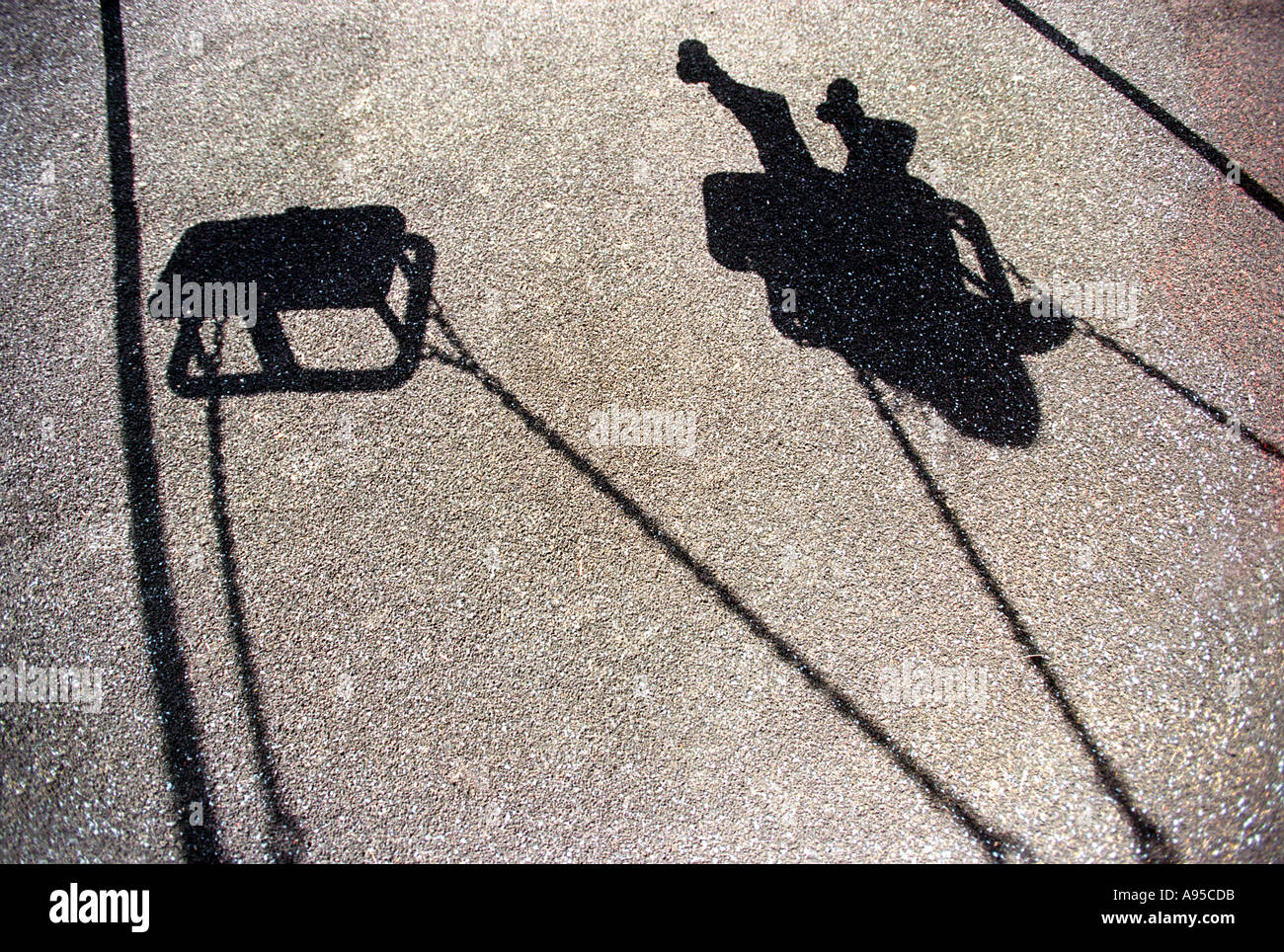 The shadow of a young girl or boy playing on a swing Stock Foto
