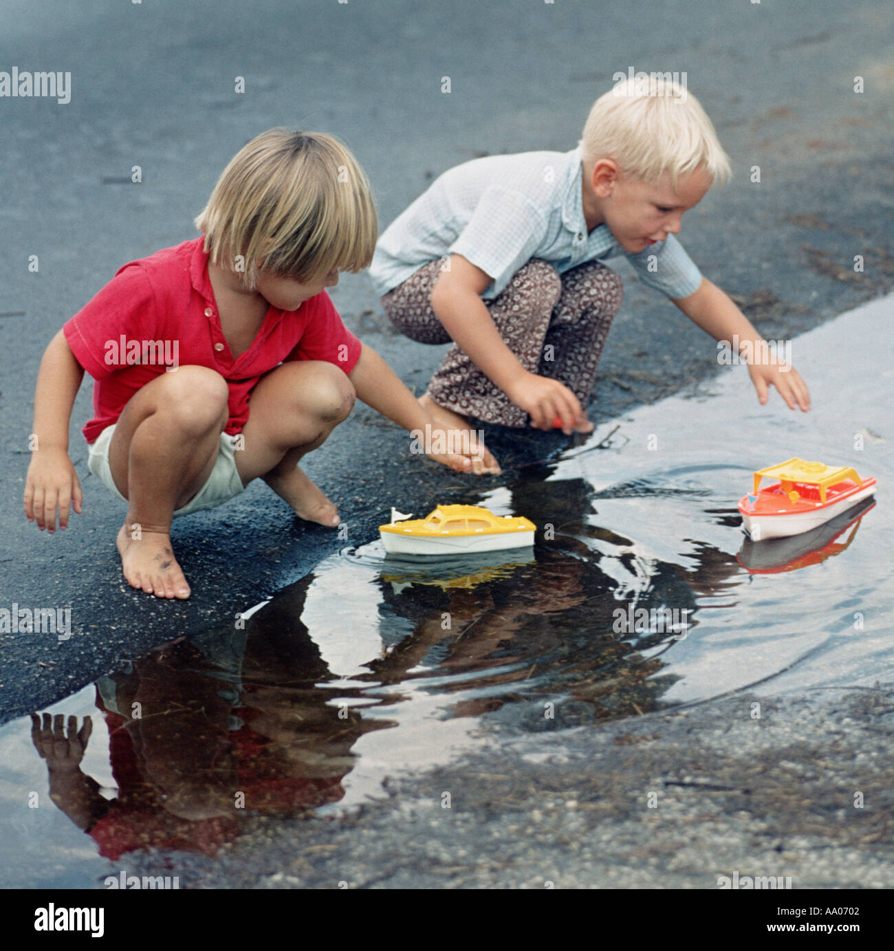 Lillle Boy Toys Boats : Two boys playing with toy boats in puddle of water stock