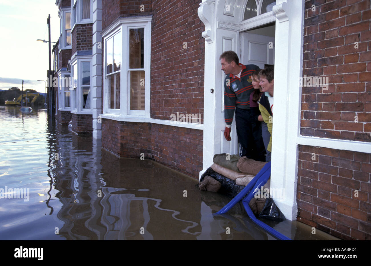 Family in flooded house look out of front door onto for Outer look of house