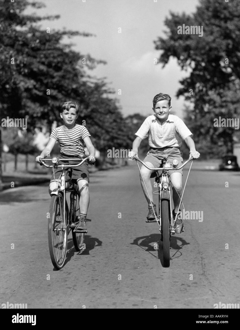 1930s 1940s TWO BOYS RIDING BIKES ON TREE LINED STREET ...