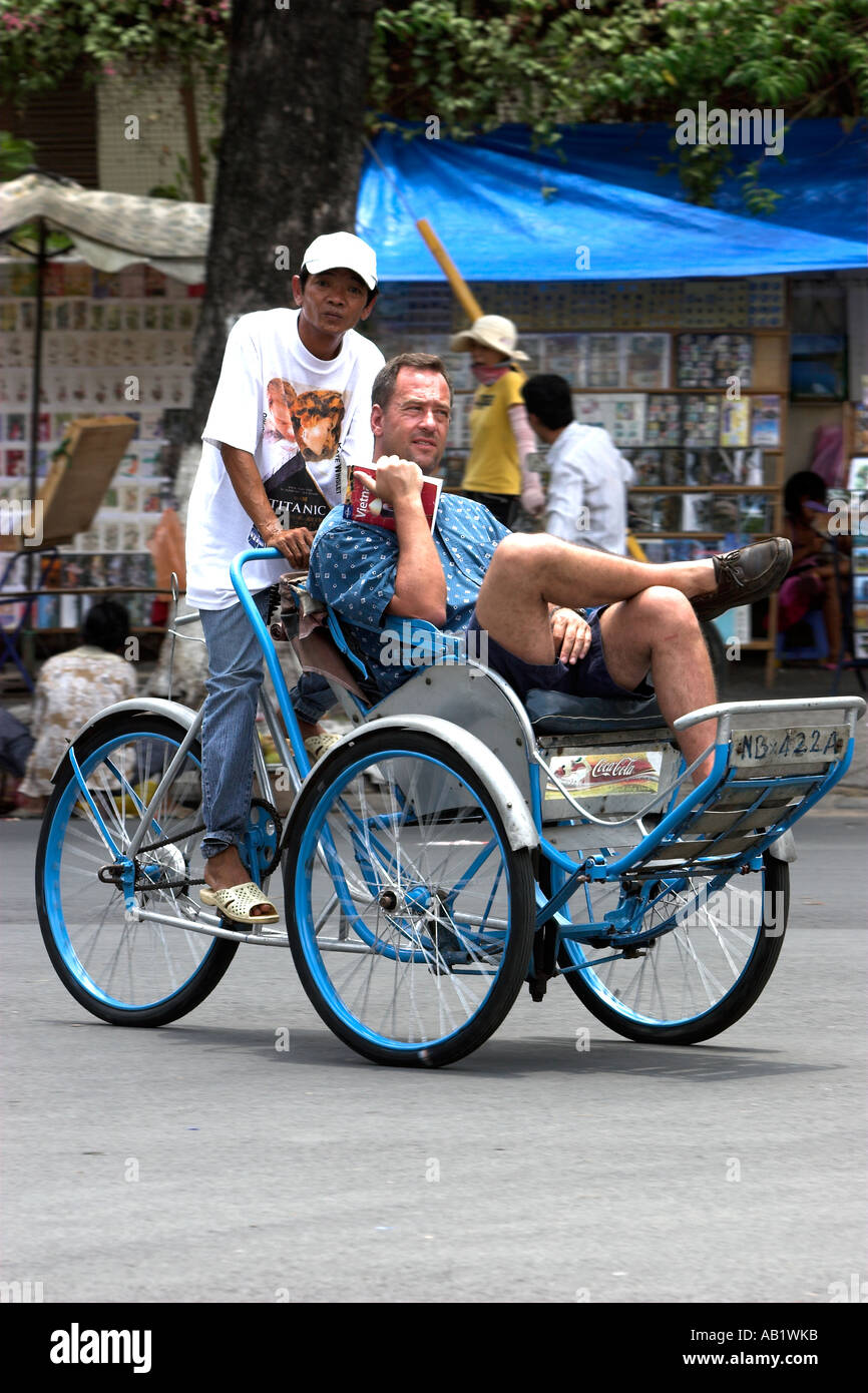 Stock Photo - Male visitor tours Ho Chi Minh City by cyclo rickshaw Vietnam