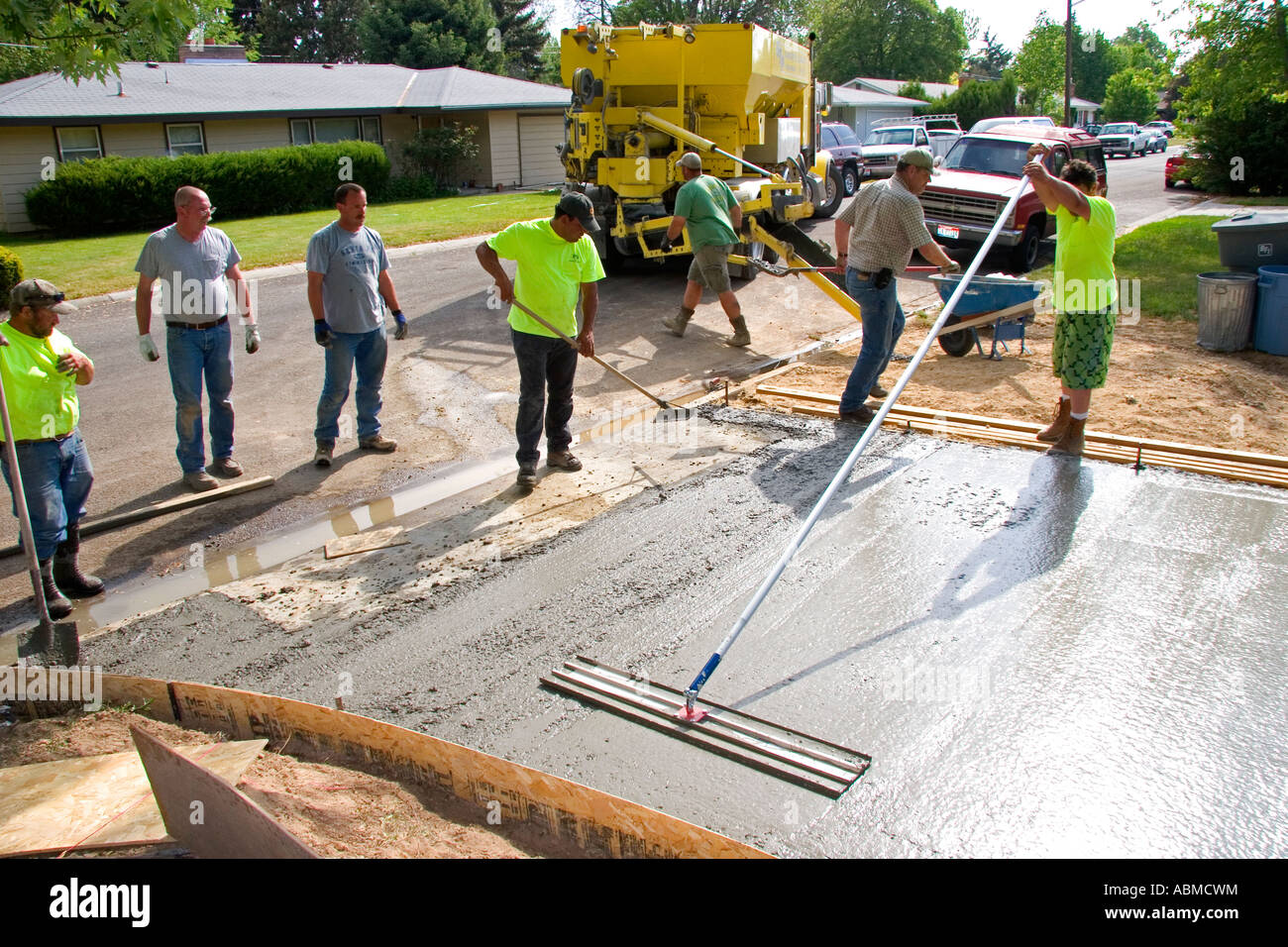Workers pouring and leveling a concrete driveway in boise for How to pour a concrete driveway