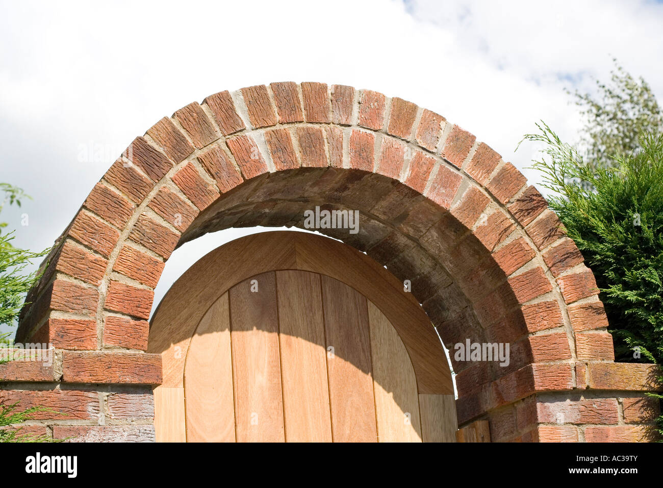 Curved Red Brick Arch Over Garden Gateway With Wooden Door
