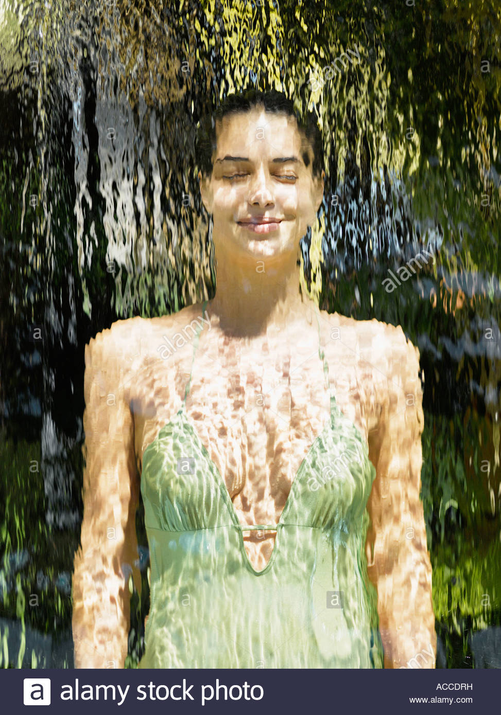 Woman in a bathing suit behind a waterfall Stock Photo
