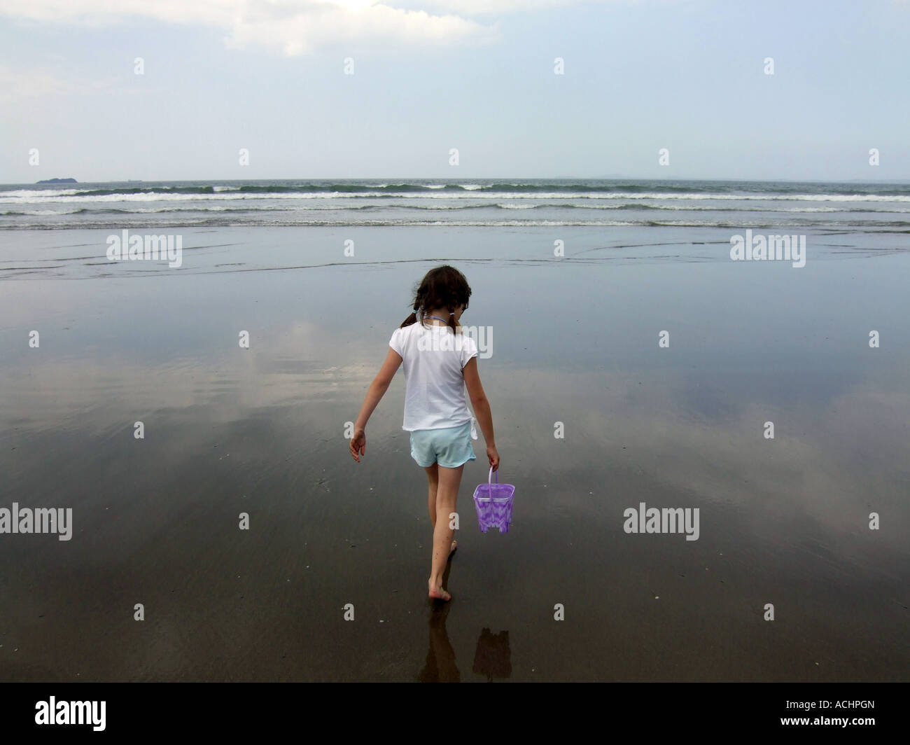 Girl walking out to the sea carrying a bucket, UK Stock Foto