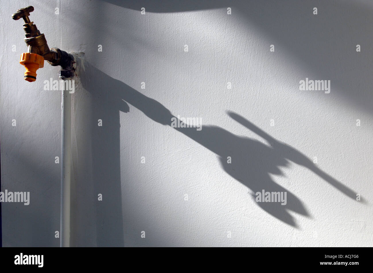 the-shadow-of-a-greenhouse-water-tap-on-