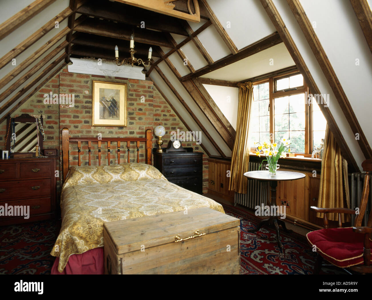 Wooden chest below bed in attic bedroom with brick wall for Wooden attic box bed