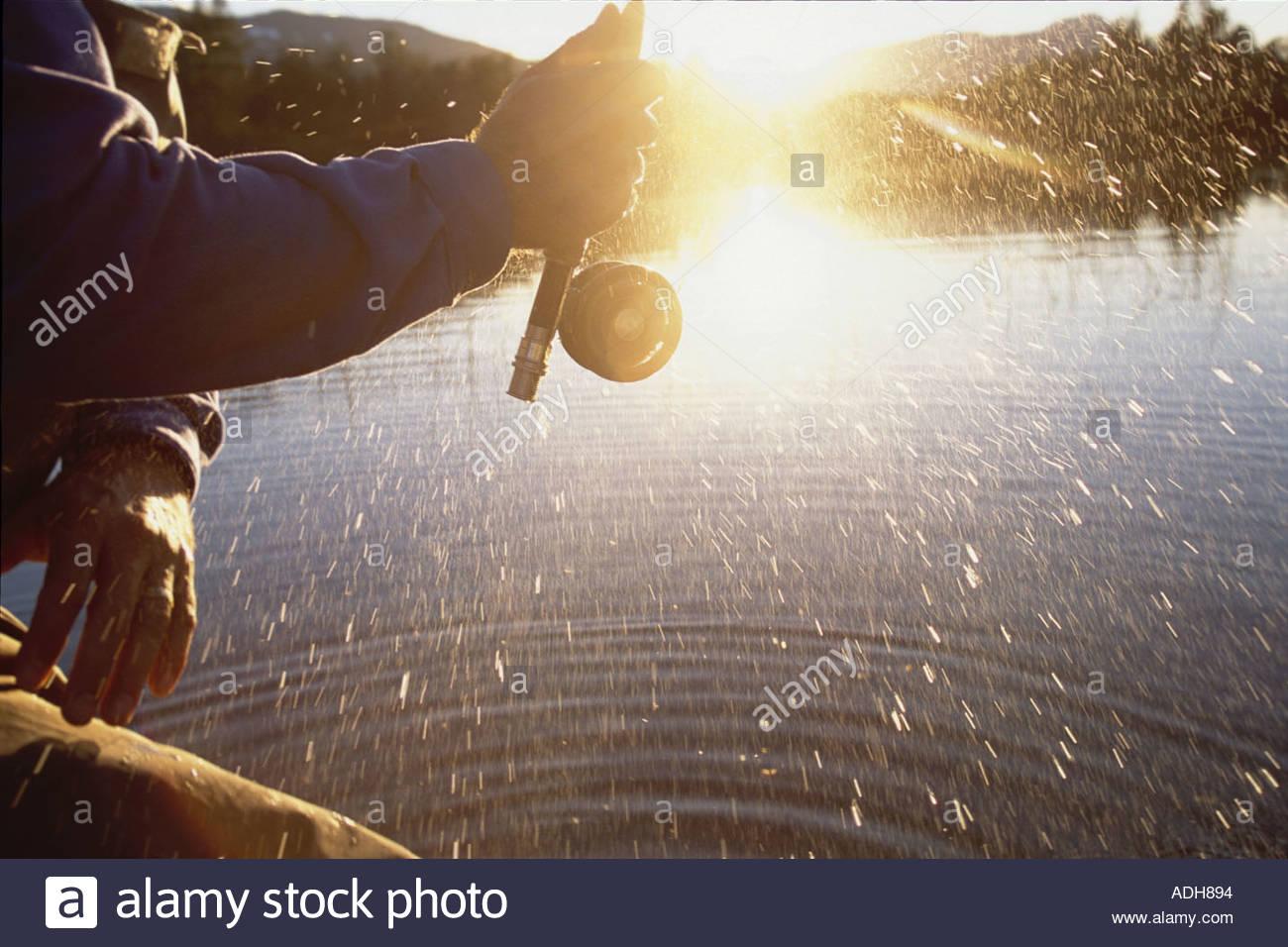 Man Flyfishing in Portage w Closeup of Reel Spinning AK Summer Stock Foto