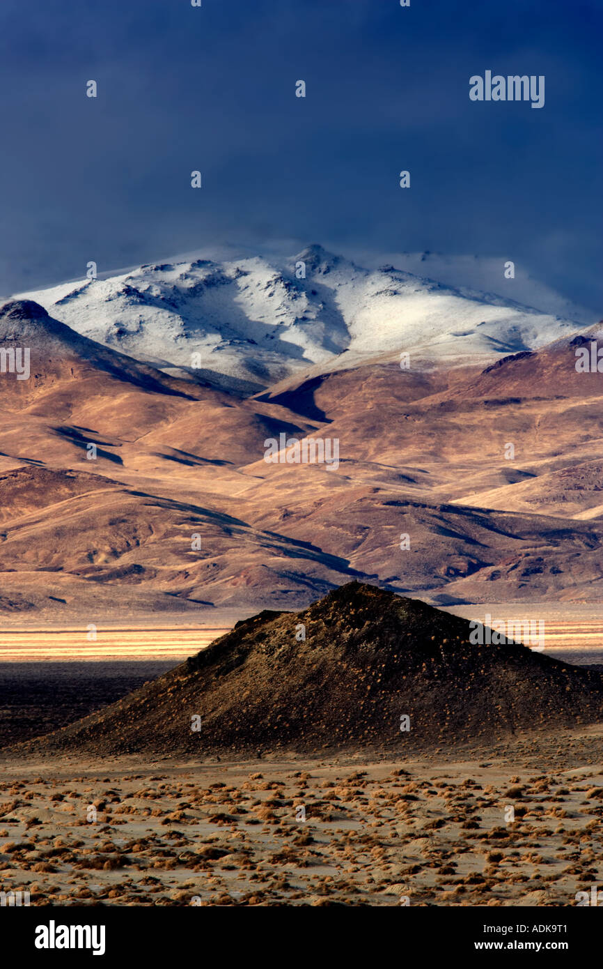 Small cinder cone and snow covered mountains Black Rock Desert National Conservation Area Nevada Stock Foto