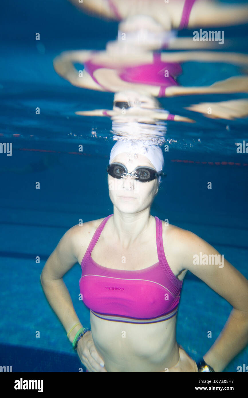 water sport woman in purple swim suit doing exercise underwater in a stock photo royalty free