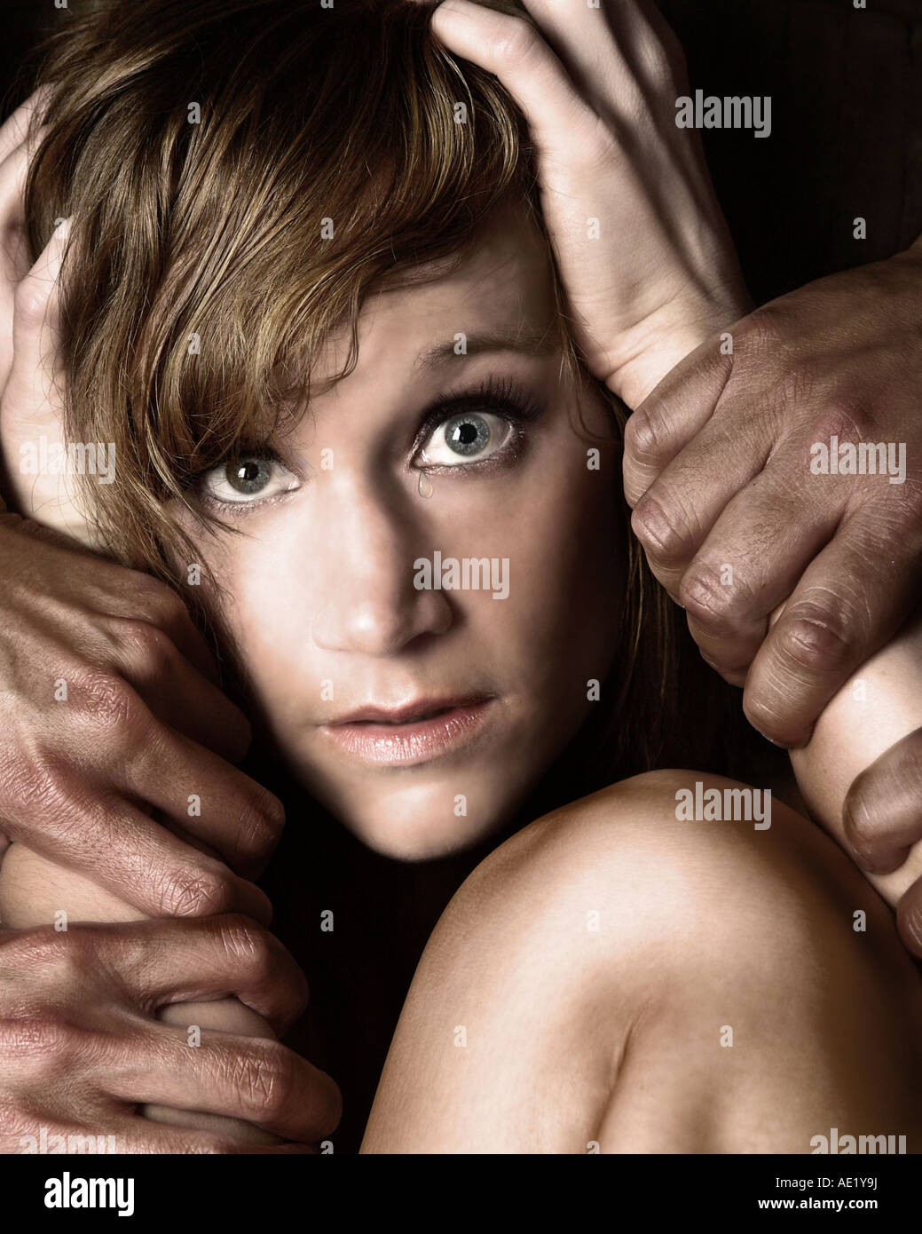 A young girl grabbing at her hair while several hands grab at her arms. Stock Photo