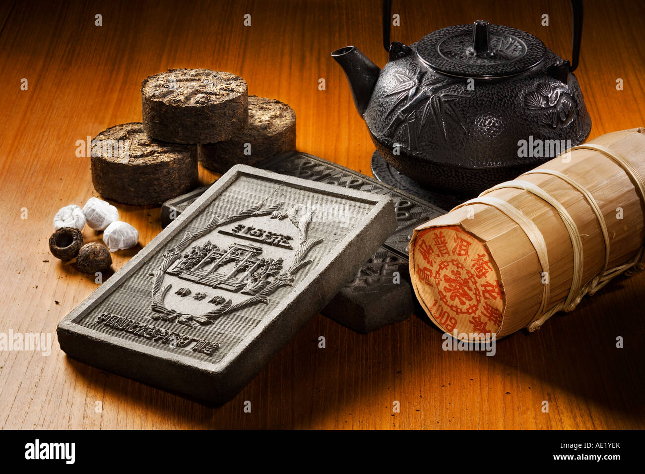 A tea kettle, tea bricks and tea rolls wrapped in fancy packaging placed on a table top. Stock Photo