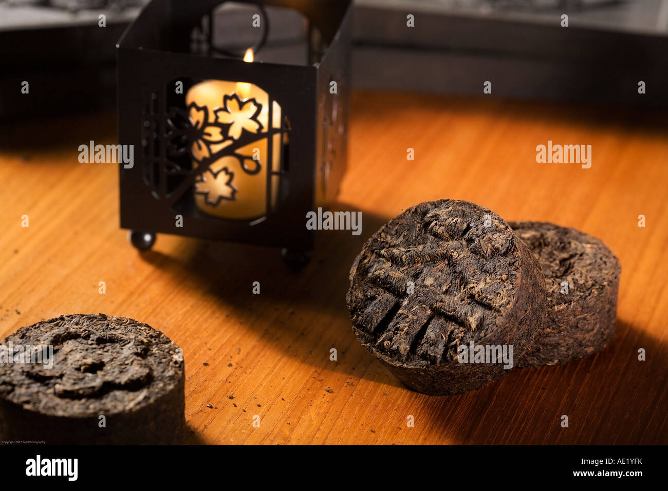 Tea rolls on a table adorned with distinct designs near a lit candle. Stock Photo