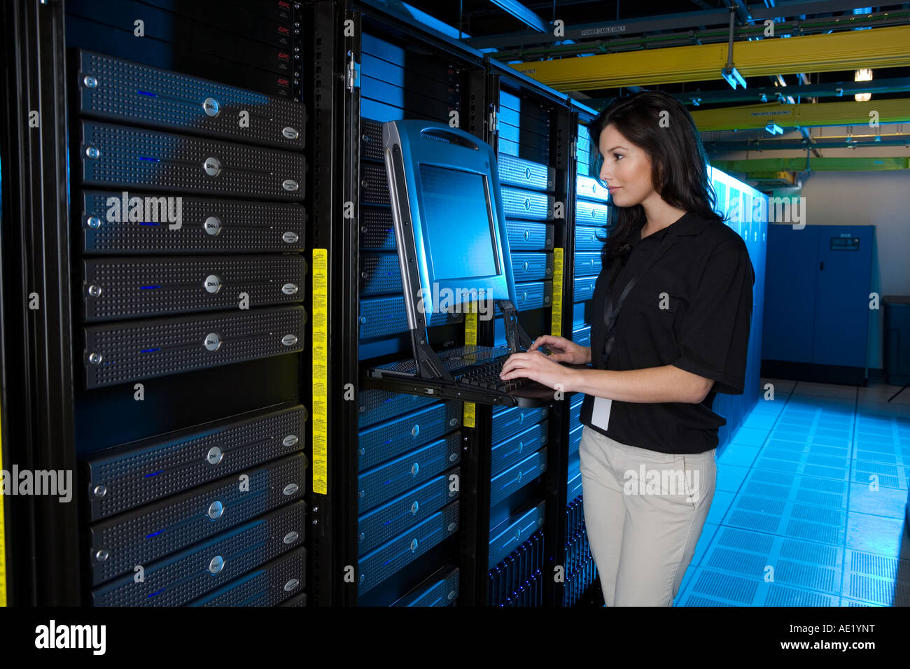 A young woman stands at a computer in a warehouse filled with servers. Stock Photo