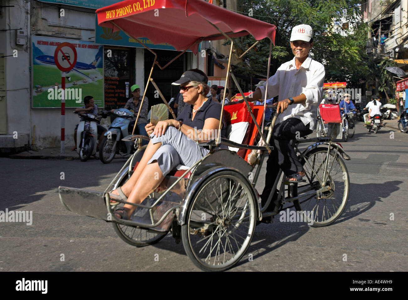 Stock Photo - Visitor tours Hanoi Old Quarter by cyclo rickshaw Vietnam