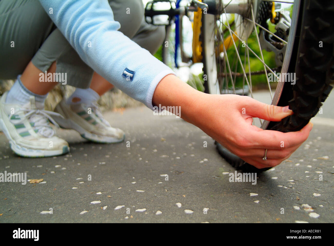 woman checking for a flat tire on her bike Stock Photo