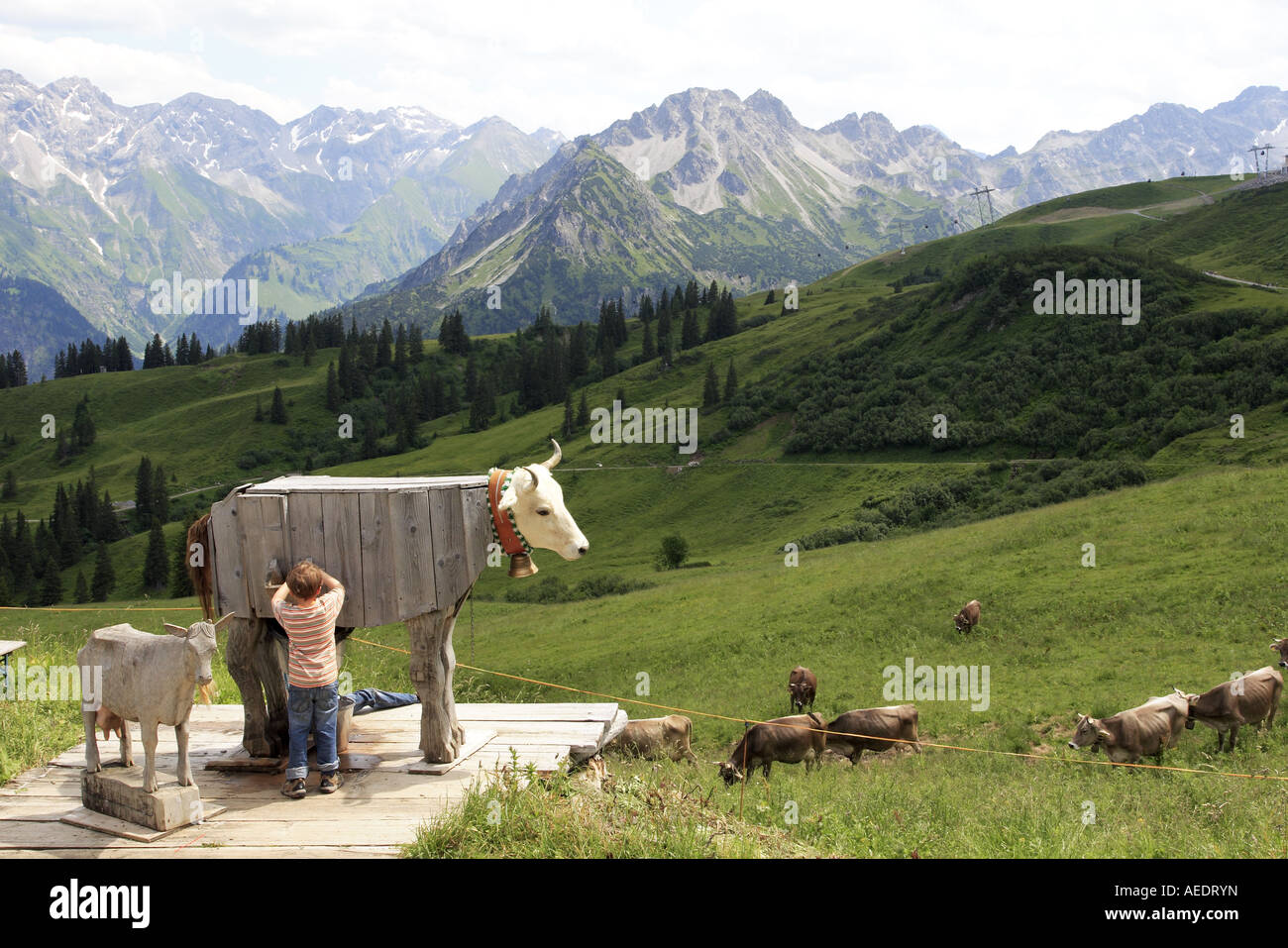 boy-playing-at-milking-a-wooden-cow-on-t