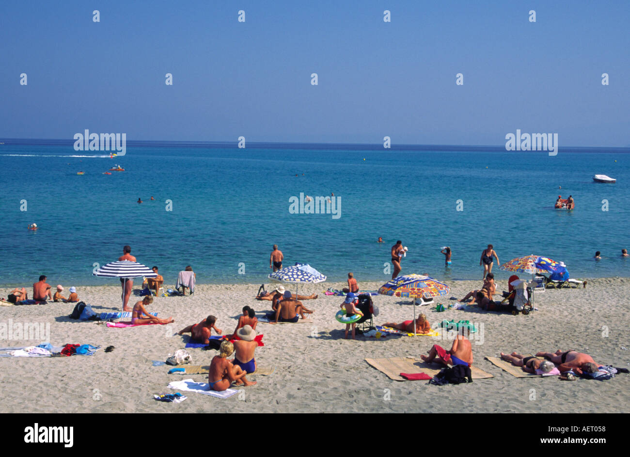 Holiday makers sunbathing on the beach beside the Aegean ...
