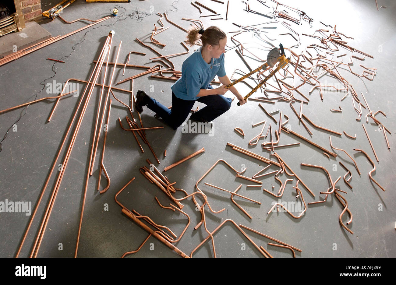 A Young Girl Training To Be A Plumber With Copper Pipes