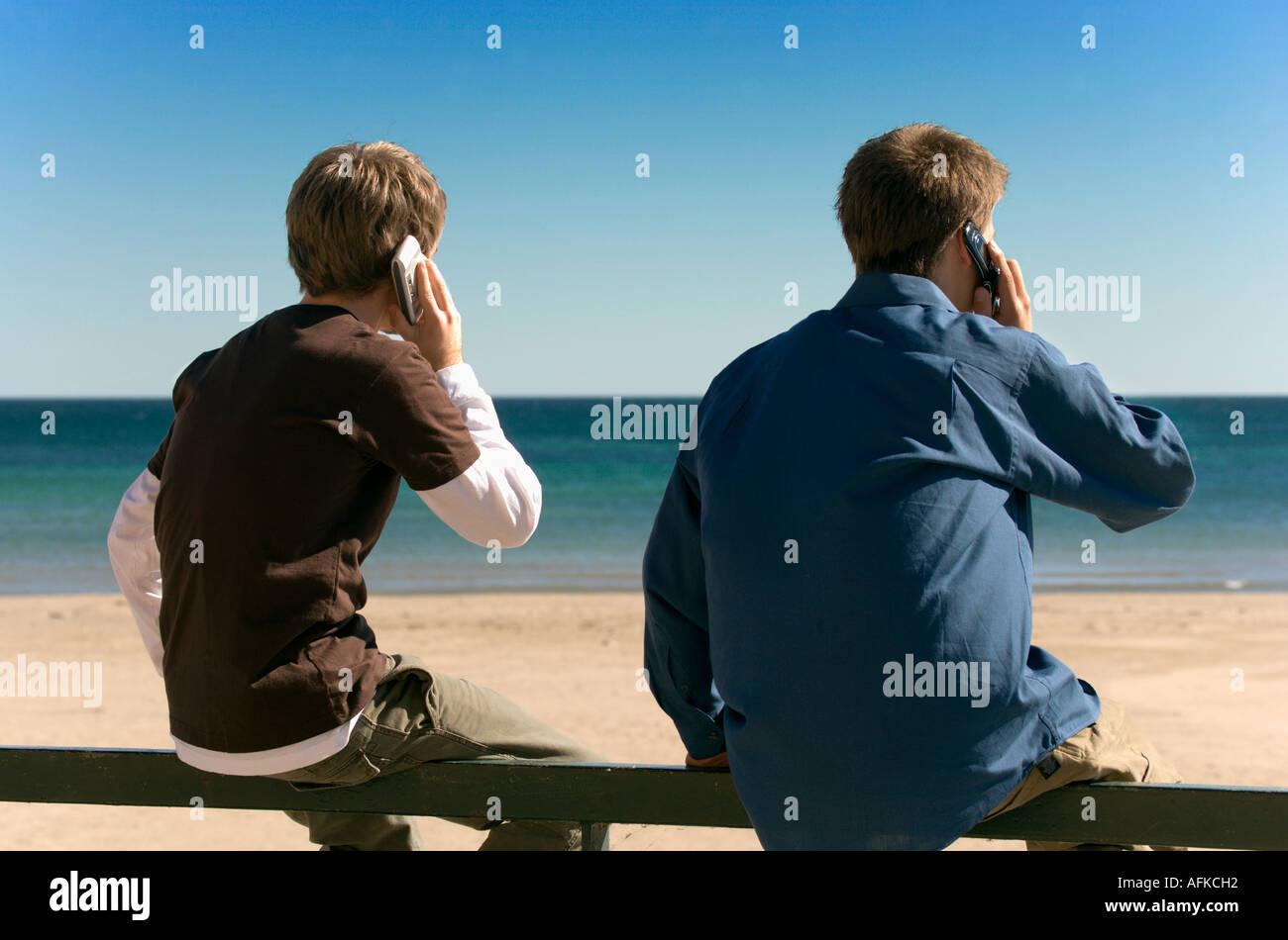 teenage-boys-using-mobile-phones-at-lake