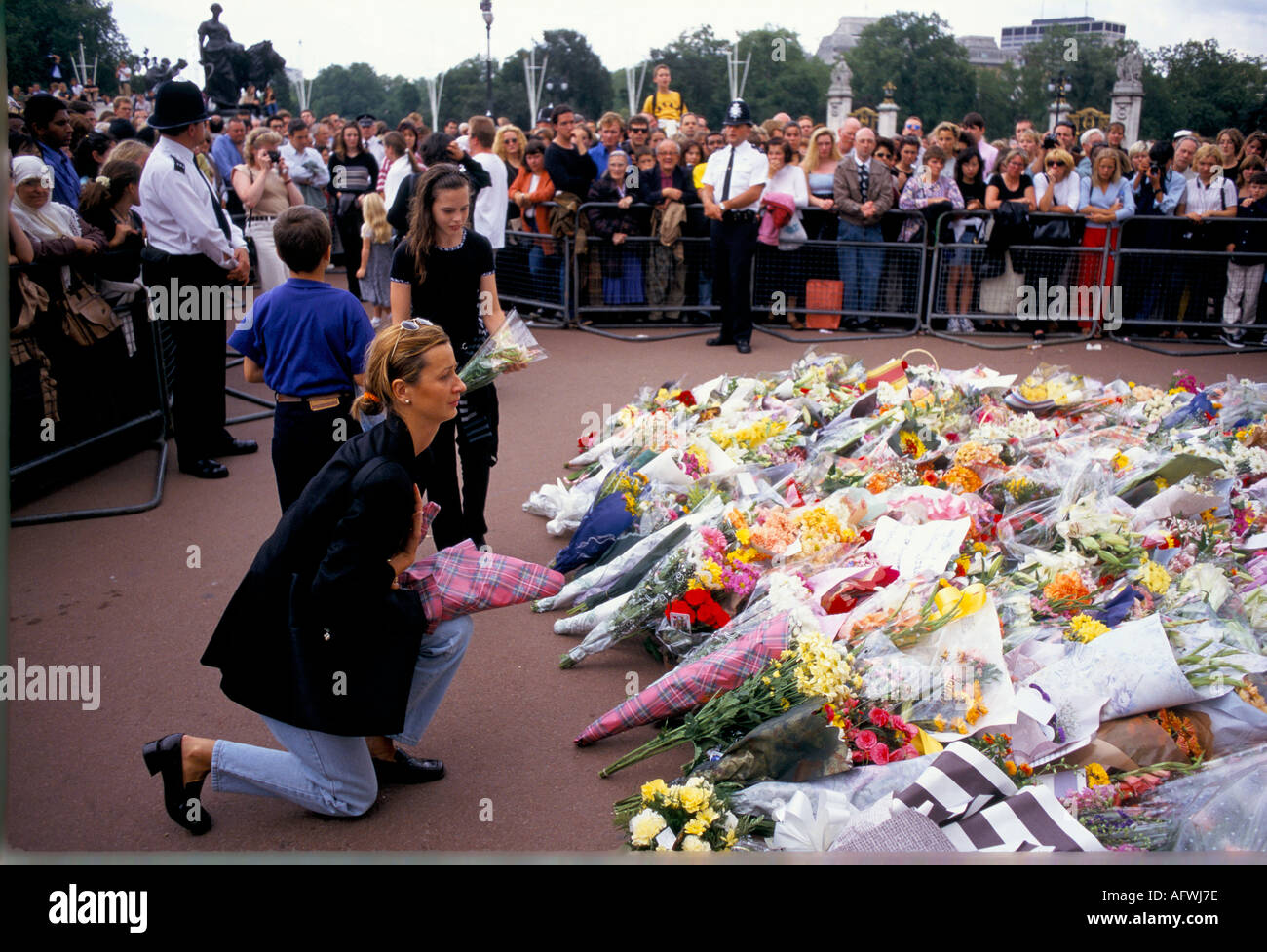 WOMAN KNEELS WHILE LAYING FLOWERS FOR DIANA  AT BUCKINGHAM PALACE LONDON 1997 Stock Foto