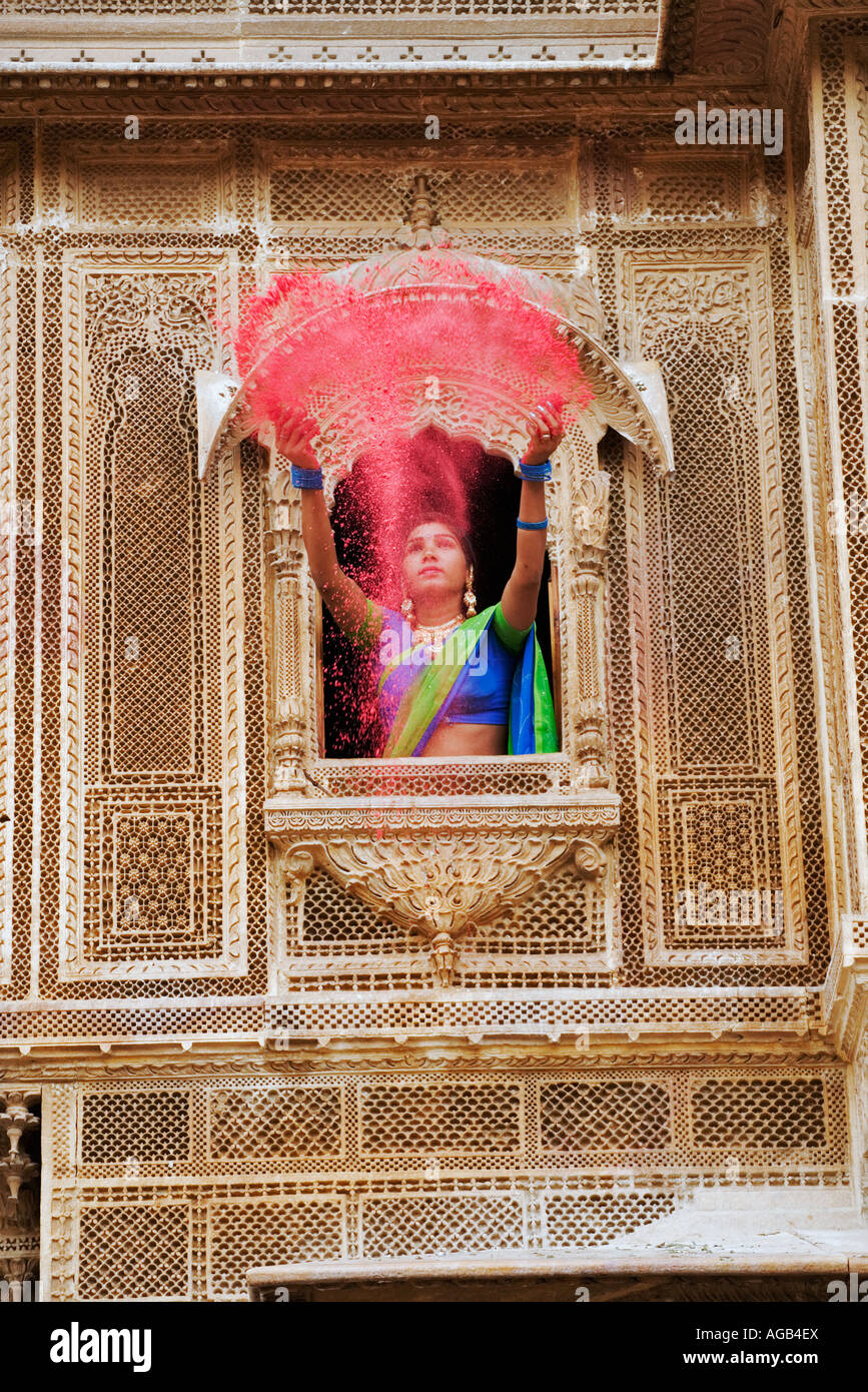 Woman throwing brightly coloured holi powder through a window of a haveli Stock Foto